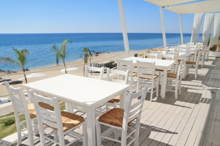 Typical greek tavern - cafe on balcony, by the mediterranean sea Standard-Bild