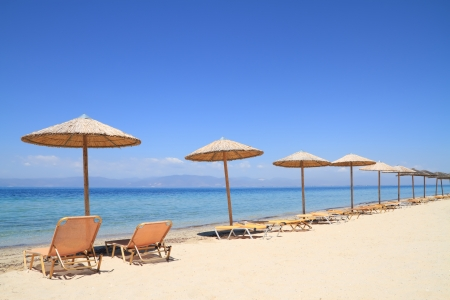 Umbrellas and recliners by the sea on exotic resort; Thassos island - Greece photo