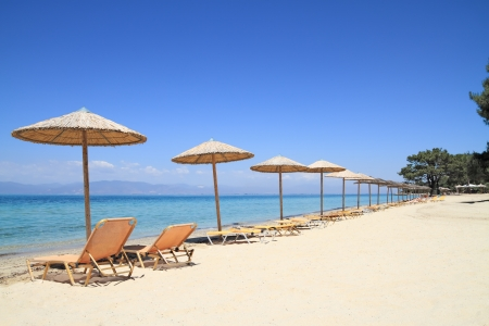 thassos: Umbrellas and recliners by the sea on exotic resort, Thassos island - Greece Stock Photo