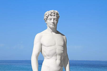 Ancient greek statue of a young athlete by the sea photo