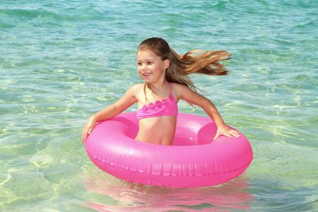 Happy girl with lifebuoy enjoying water Standard-Bild