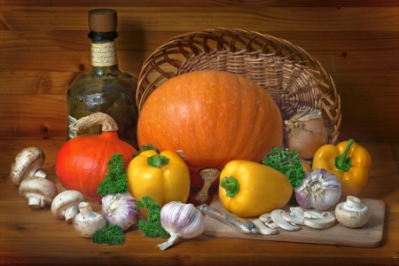 Still life of pumpkins, mushrooms, yellow pepper and parsley on a wooden table photo