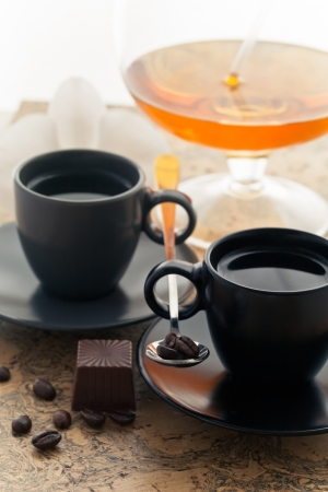 two coffee cups and coffee beans sprinkled with dessert and a glass of wine photo