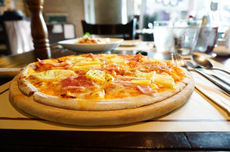 Tasty traditional hawaiian pizza on board on wooden board