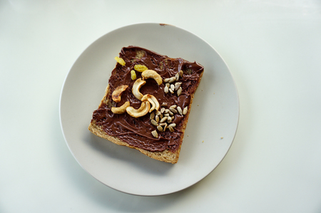 Toast bread with homemade chocolate jam and cereal served  in top view with copy space for breakfast or brunch.