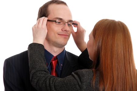 long sightedness: Young woman tries on glasses to the businessman isolated on white background