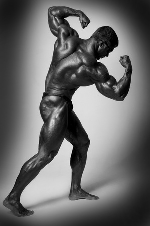 strong light: Muscled male model posing in studio on a light background