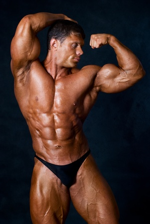 bodybuilder training: strong athletic man on black background