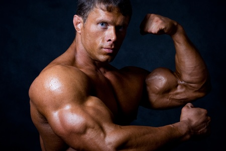 muscle men: strong athletic man on black background
