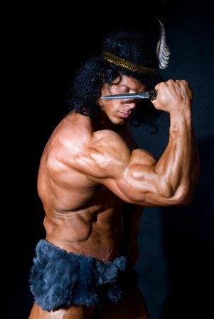 sexy muscular man: Strong athletic man with a knife on a black background Stock Photo