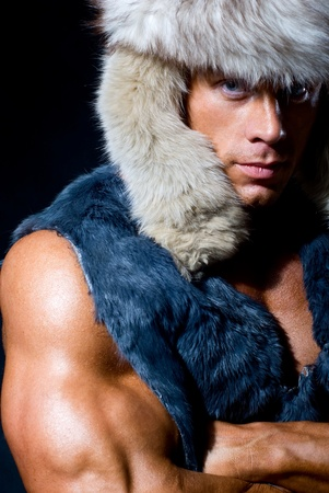 Strong athletic man in a fur cap isolated over black background Stock Photo - 11783518
