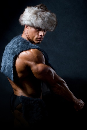 Strong athletic man in a fur cap isolated over black background Stock Photo - 11783489
