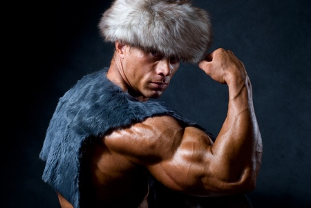 Strong athletic man in a fur cap isolated over black background Stock Photo - 11783465