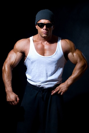 strong athletic man in dark glasses on a black background Stock Photo - 11783400
