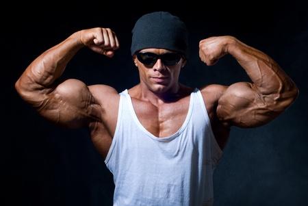 culturista: hombre fuerte de atletismo en gafas oscuras sobre un fondo negro Foto de archivo