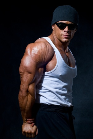 strong athletic man in dark glasses on a black background Stock Photo - 11783409