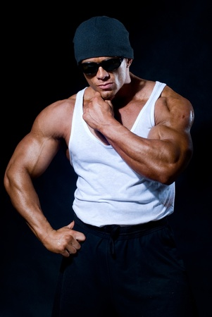 strong athletic man in dark glasses on a black background Stock Photo - 11783433