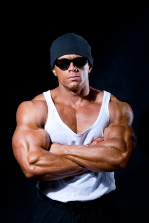 strong athletic man in dark glasses on a black background