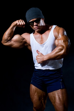 strong athletic man in dark glasses on a black background Stock Photo - 11783383