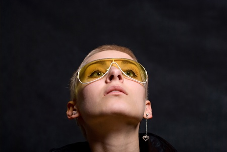 The young girl in a leather jacket and yellow glasses photo