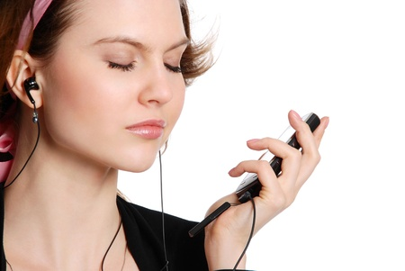 The girl listens to music in ear-phones isolated on the white background Standard-Bild