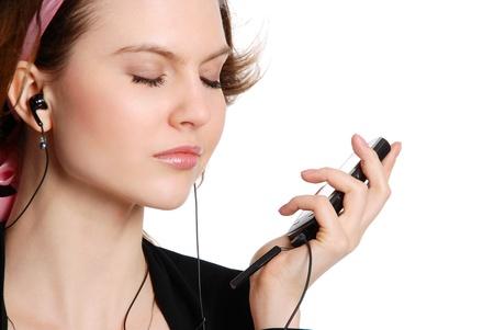 escuchando musica: La niña escucha música en auriculares aislados en el fondo blanco Foto de archivo