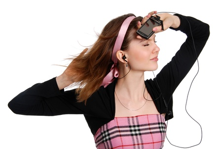 The girl listens to music in ear-phones isolated on the white background photo