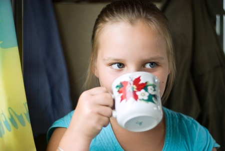 The girl drinks from a cup and distracts