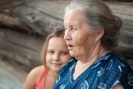 The elderly woman with the grand daughter against the wooden house photo