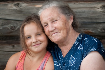 The elderly woman with the grand daughter against the wooden house Stock Photo