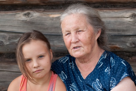 grand daughter: The elderly woman with the grand daughter against the wooden house Stock Photo