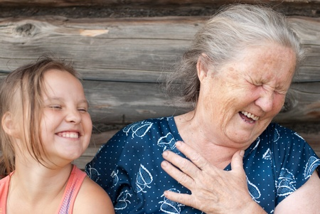 grand child: The elderly woman with the grand daughter against the wooden house Stock Photo