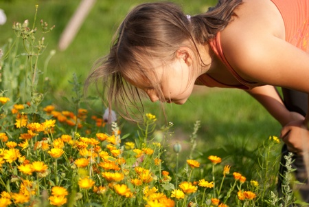 smells: The girl smells orange flowers
