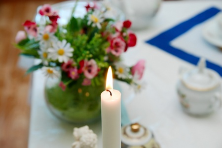 Burning candle on a festive table photo