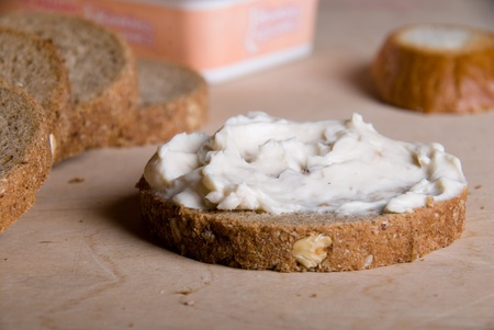 sandwich spread: Piece of bread with a cheese cream on a wooden table