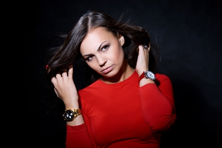 The beautiful girl with a wrist watch against a dark background photo