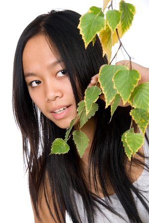 philippine adult: The young Vietnamese girl looks out because of a birch branch,isolated on white background Stock Photo