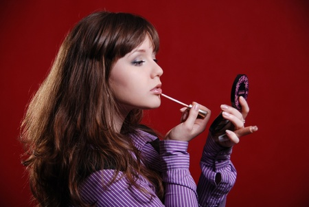 Young woman applying lip gloss a red background photo