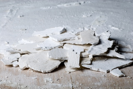 Pieces of old plaster on a wooden surface photo