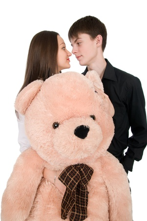 Beautiful young pair with a teddy bear isolated on white background photo