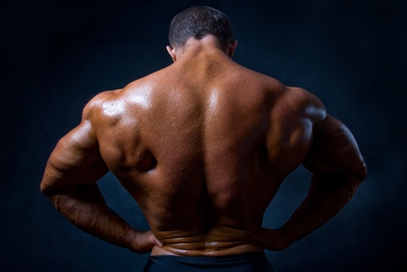 back muscles: strong athletic man on black background