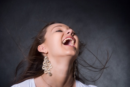 The young, beautiful girl with a flying hair, an open mouth and on a gray background Stock Photo - 12861230