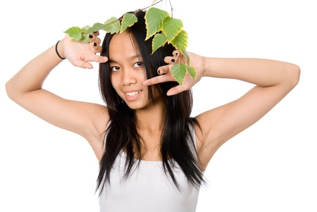 philippine adult: The young Vietnamese girl looks out because of a birch branch isolated on white background