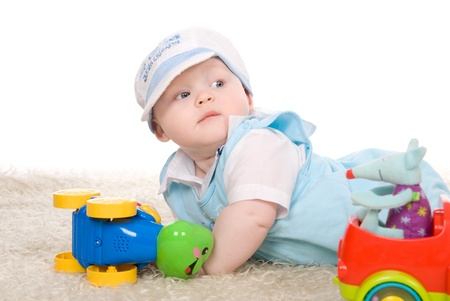 Cute little child is playing with toys while sitting on floor,looking aside photo