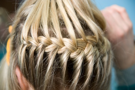 Hairdress a plait in salon photo