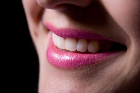 Laughing woman smile with great teeth a dark background photo