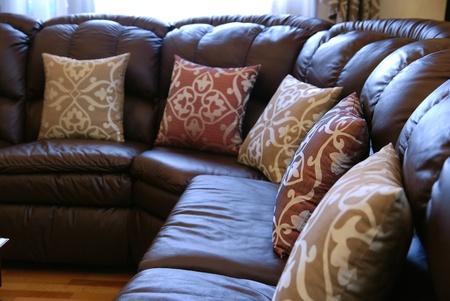 brown leather sofa: cuscini su un divano in pelle marrone Archivio Fotografico