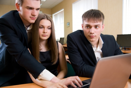 businessmeeting: Handsome young businessmen working on laptop in bright office