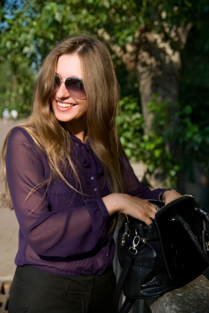 Cheerful girl with a handbag and dark glasses against trees photo