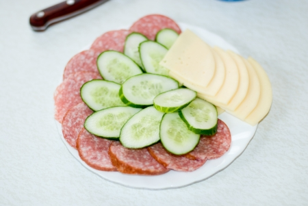Cut cheese, sausage and cucumber in a plate on a table photo